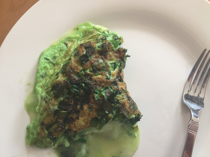 Finished green omelet on a plate with a fork before we ate it