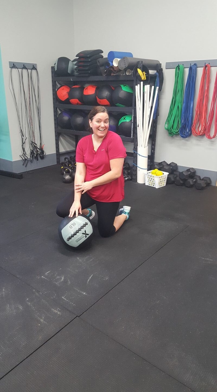 Me doing a cheesy pose with a medicine ball after EMOM burpees